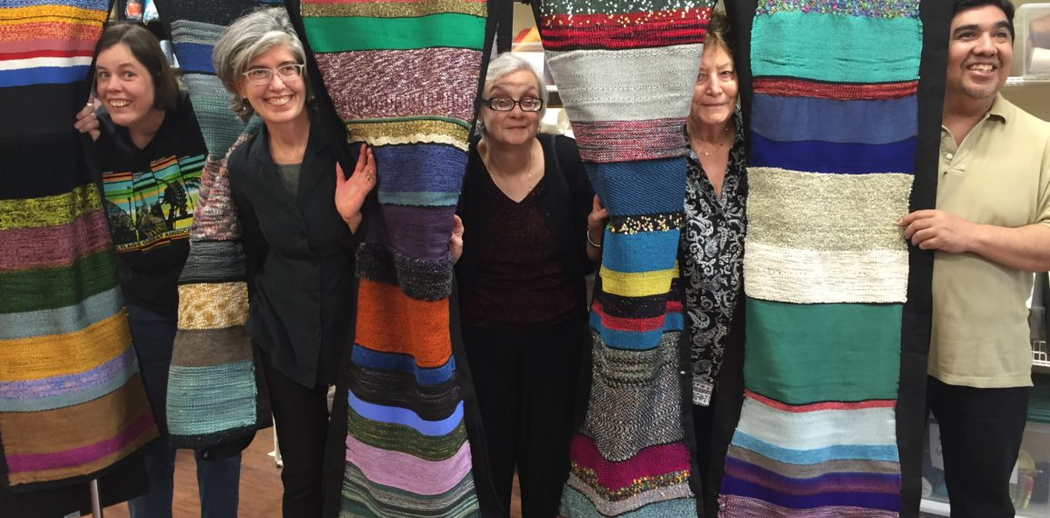 Residents and staff with hand-woven tapestries