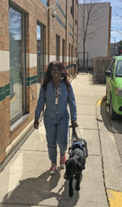 resident and her guide dog walking outside