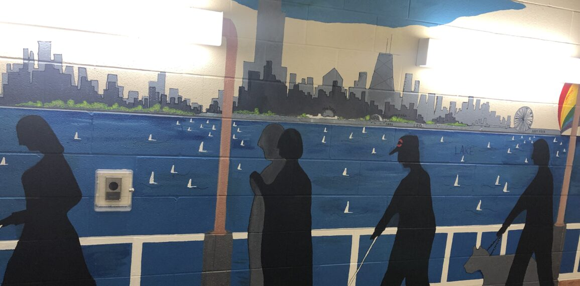 a mural depicting the lakefront and Chicago skyline, with people walking with white canes in the foreground